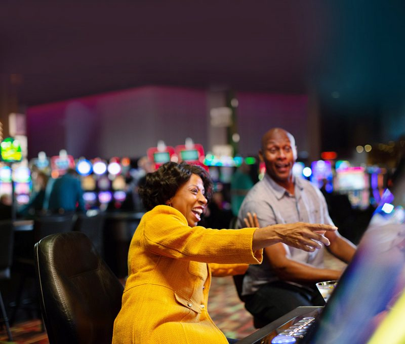 Two people playing slots